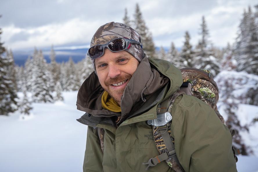 Portrait de Mathieu Hänni, l'un des accompagnateurs de Pérégrinatures sur fond de paysage enneigé.